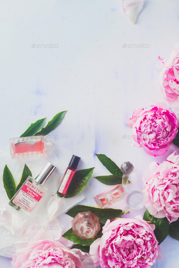 Minimal styled flat lay with peony flowers with petalsand perfume bottles on a pastel background - Stock Photo - Images