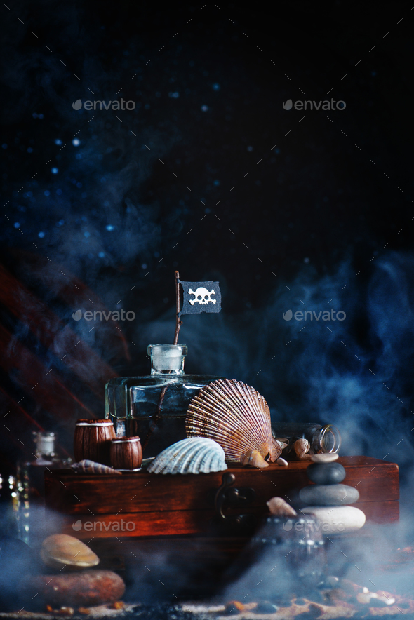 Glass bottle with pirate flag and seashells - Stock Photo - Images