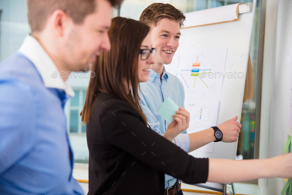 Businessman Smiling While Female Executive Holding Adhesive Note - Stock Photo - Images