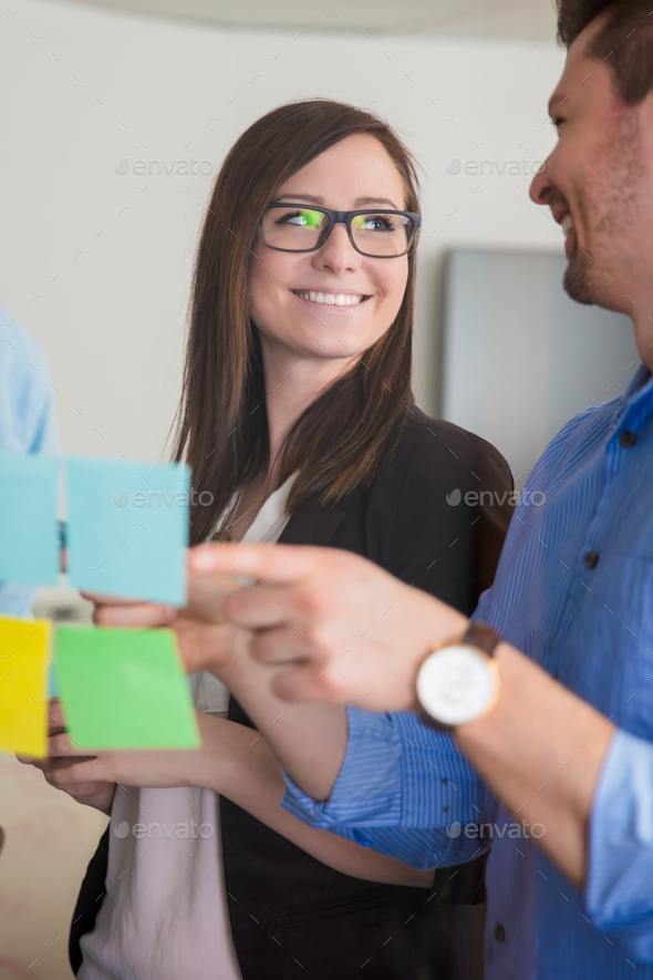 Businesswoman Looking At Colleague While Discussing Over Notes O - Stock Photo - Images