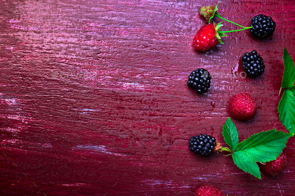 Blackberry and raspberry on red wooden background. Top view. Frame. Flat lay - Stock Photo - Images