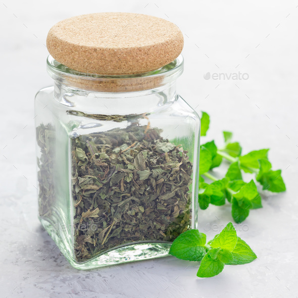 Dry herbal mint tea in a glass jar with fresh peppermint on background, square format - Stock Photo - Images