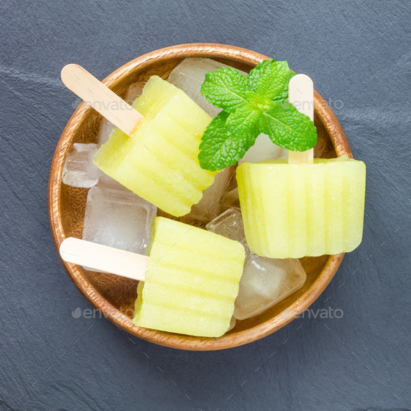Homemade melon popsicles on grey slate, top view, square - Stock Photo - Images