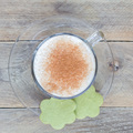 Coffee latte in glass cup with matcha cookies, top view, square format