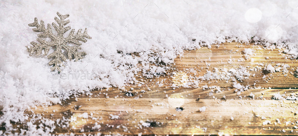 Christmas snowflake on a wooden desk, snowy bokeh background - Stock Photo - Images