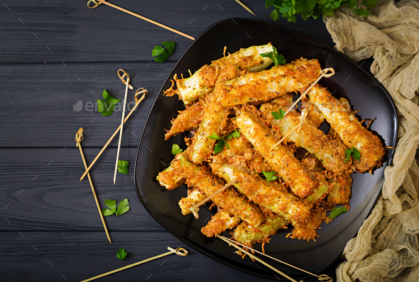 Zucchini slices baked under cheese breading - Stock Photo - Images