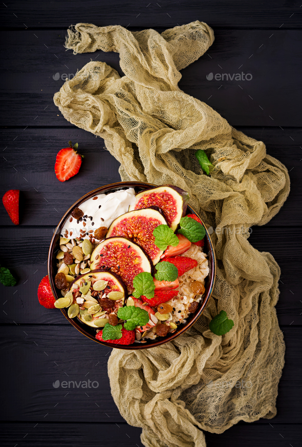 Delicious and healthy oatmeal with figs, seeds, strawberry and yogurt - Stock Photo - Images