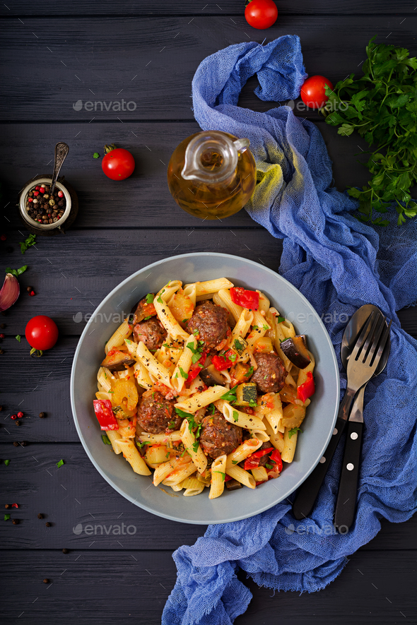 Penne pasta with meatballs in tomato sauce and vegetables in bowl - Stock Photo - Images
