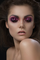 Closeup portrait of beautiful woman with violet makeup on eyes