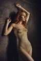 Red haired woman in beige bodysuit posing on background gray wall