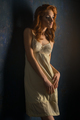 Red haired woman in white dress with expressive makeup