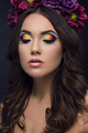 Closeup portrait of beautiful woman with colorful makeup on eyes and flowers on head
