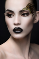 Close up portrait of woman with expressive makeup, black lips and decorations on eyebrow