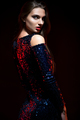 Gorgeous young woman in fashion dress posing on dark background