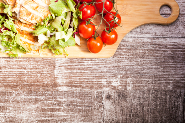 Grilled chicken breast on fresh cut salad next to a brunch of to - Stock Photo - Images