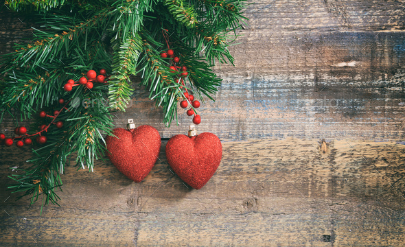 Christmas red hearts and green garland on a wooden board - Stock Photo - Images