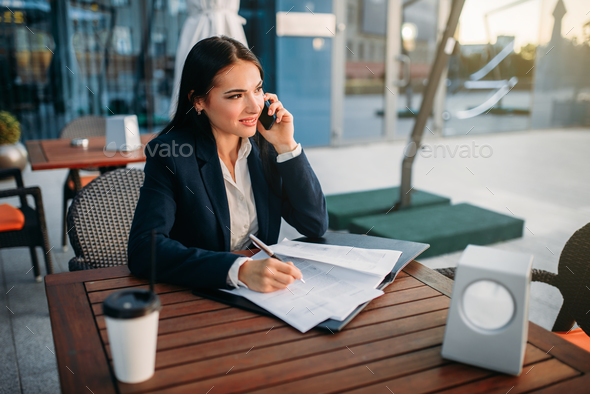Business woman talks by mobile phone in cafe - Stock Photo - Images