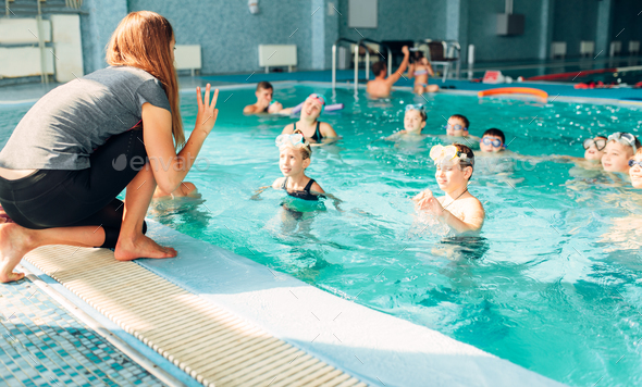 Instructor works with children in swimming pool