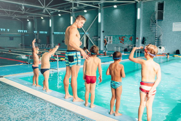 Instructor with children stands near water - Stock Photo - Images