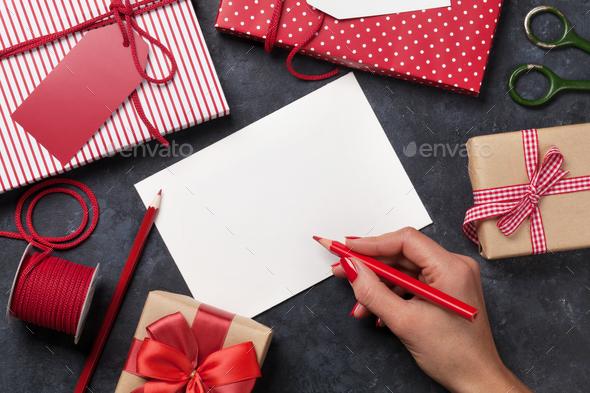 Female writing christmas greeting card - Stock Photo - Images