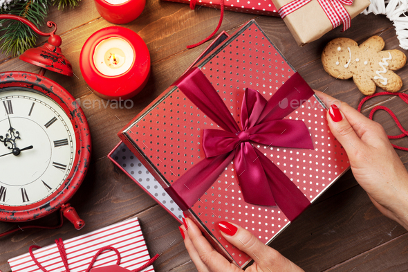 Female hands opening christmas gift - Stock Photo - Images