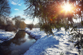 Winter landscape by a river during sunset
