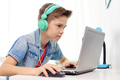 boy in headphones playing video game on laptop - PhotoDune Item for Sale