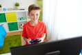 boy with gamepad playing video game on computer - PhotoDune Item for Sale