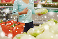 woman with basket and chinese cabbage at grocery