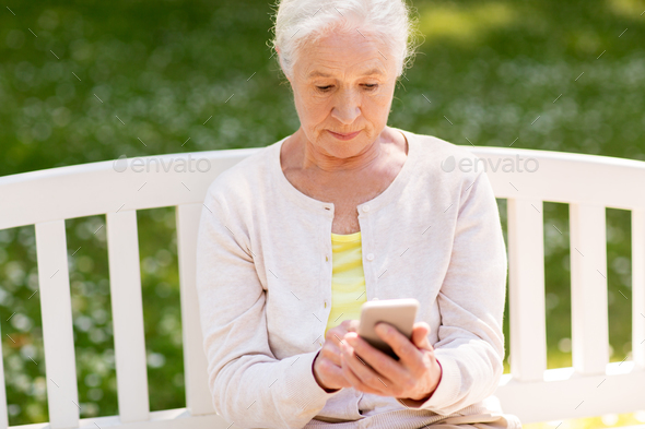 senior woman with smartphone at summer park - Stock Photo - Images
