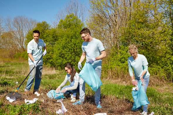 volunteers with garbage bags cleaning park area - Stock Photo - Images