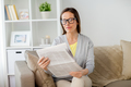 woman in glasses reading newspaper at home - PhotoDune Item for Sale