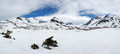 Panorama: Snowy Rocky Mountain and White Clouds on Blue Sky