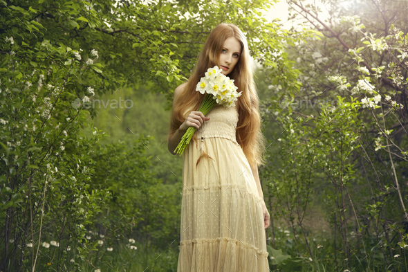 Portrait a beautiful young woman with flowers in the garden - Stock Photo - Images