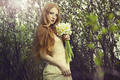 Portrait a beautiful young woman with flowers in the garden