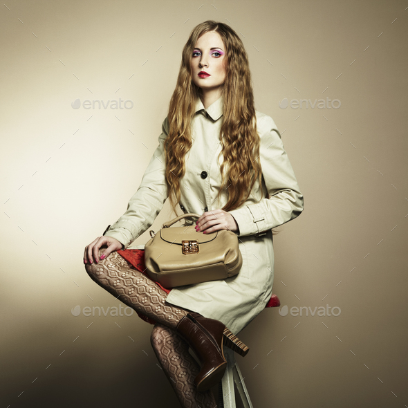 Portrait of a beautiful young woman with a handbag - Stock Photo - Images