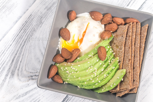 Poached egg with avocado and almonds - Stock Photo - Images
