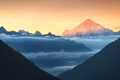 Mountains and low clouds at colorful sunrise in Nepal - PhotoDune Item for Sale