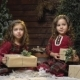 Little Sisters in Dresses Are Sitting with Presents in the Christmas Room and the Snow Is Falling on