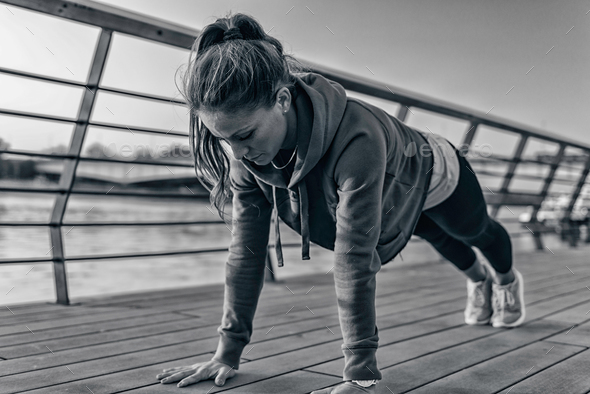Woman doing plank on riverside - Stock Photo - Images