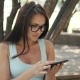Beautiful Cheerful Girl With a Tablet PC Sitting In a Park on a Bench on a Sunny Day - VideoHive Item for Sale