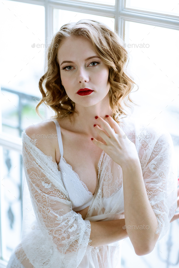 Fashionable female portrait of cute lady in white robe indoors - Stock Photo - Images
