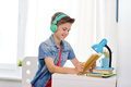 student boy in headphones reading book at home