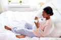 pregnant woman eating yogurt in bed