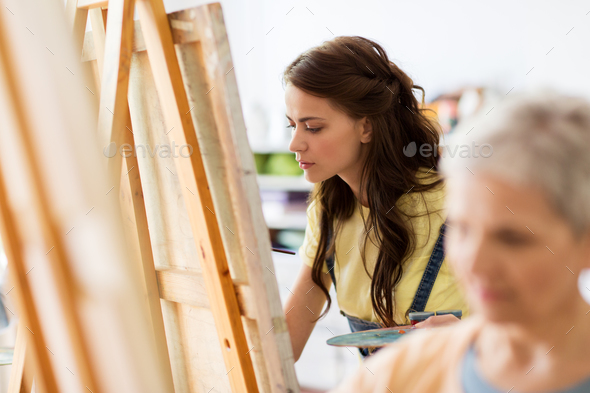 student girl with easel painting at art school - Stock Photo - Images