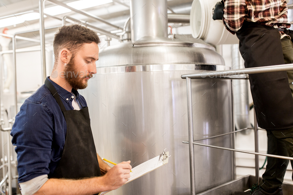 men working at craft brewery or beer plant - Stock Photo - Images