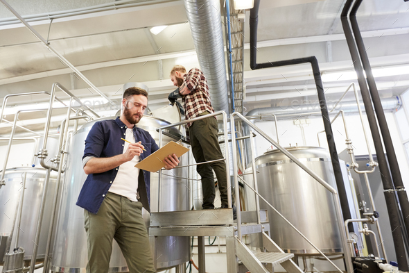 men with clipboard at brewery or beer plant - Stock Photo - Images