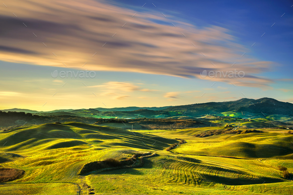Volterra winter panorama, rolling hills and green fields on suns - Stock Photo - Images