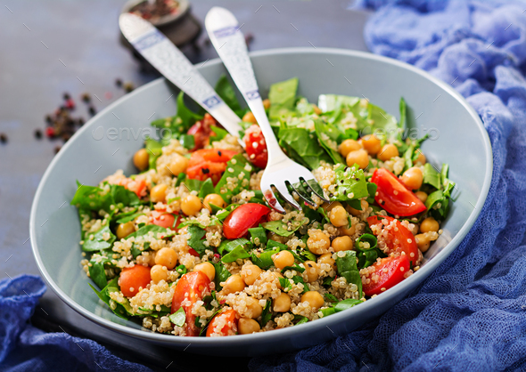 Healthy vegan salad of fresh vegetables - tomatoes, chickpeas, spinach and quinoa - Stock Photo - Images