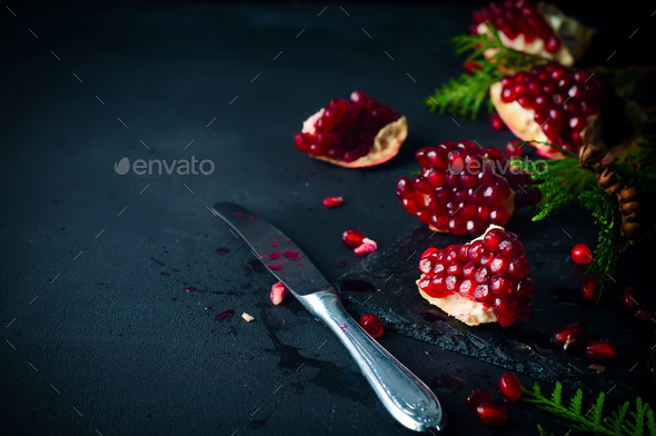Half pomegranate and seeds a branch of spruce - Stock Photo - Images